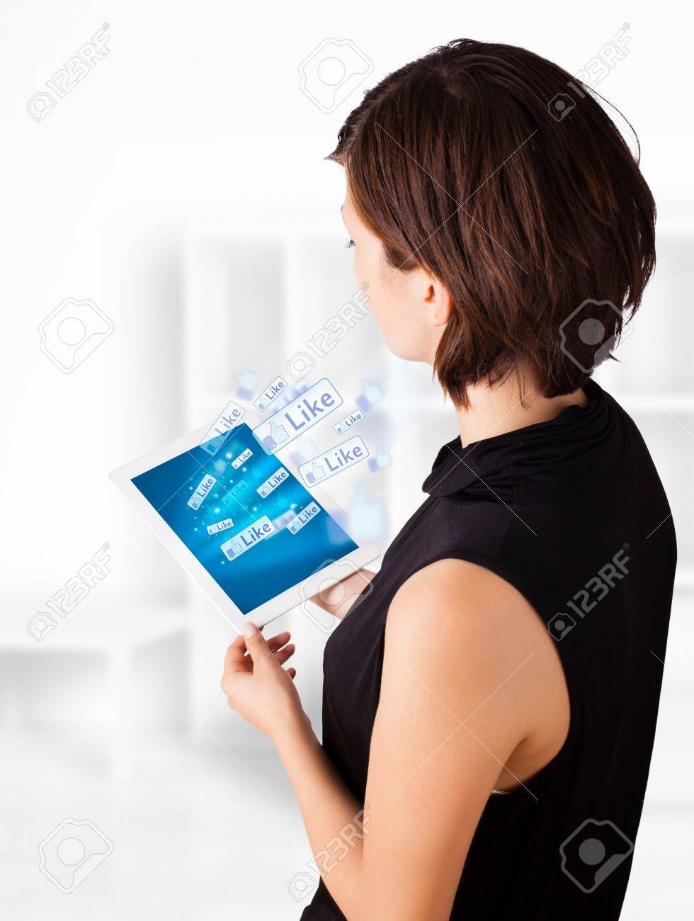 Young business woman looking at modern tablet with social icons Stock Photo - 16290826