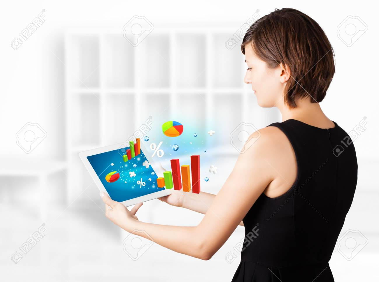 Young business woman looking at modern tablet with colourful diagrams Stock Photo - 16367754