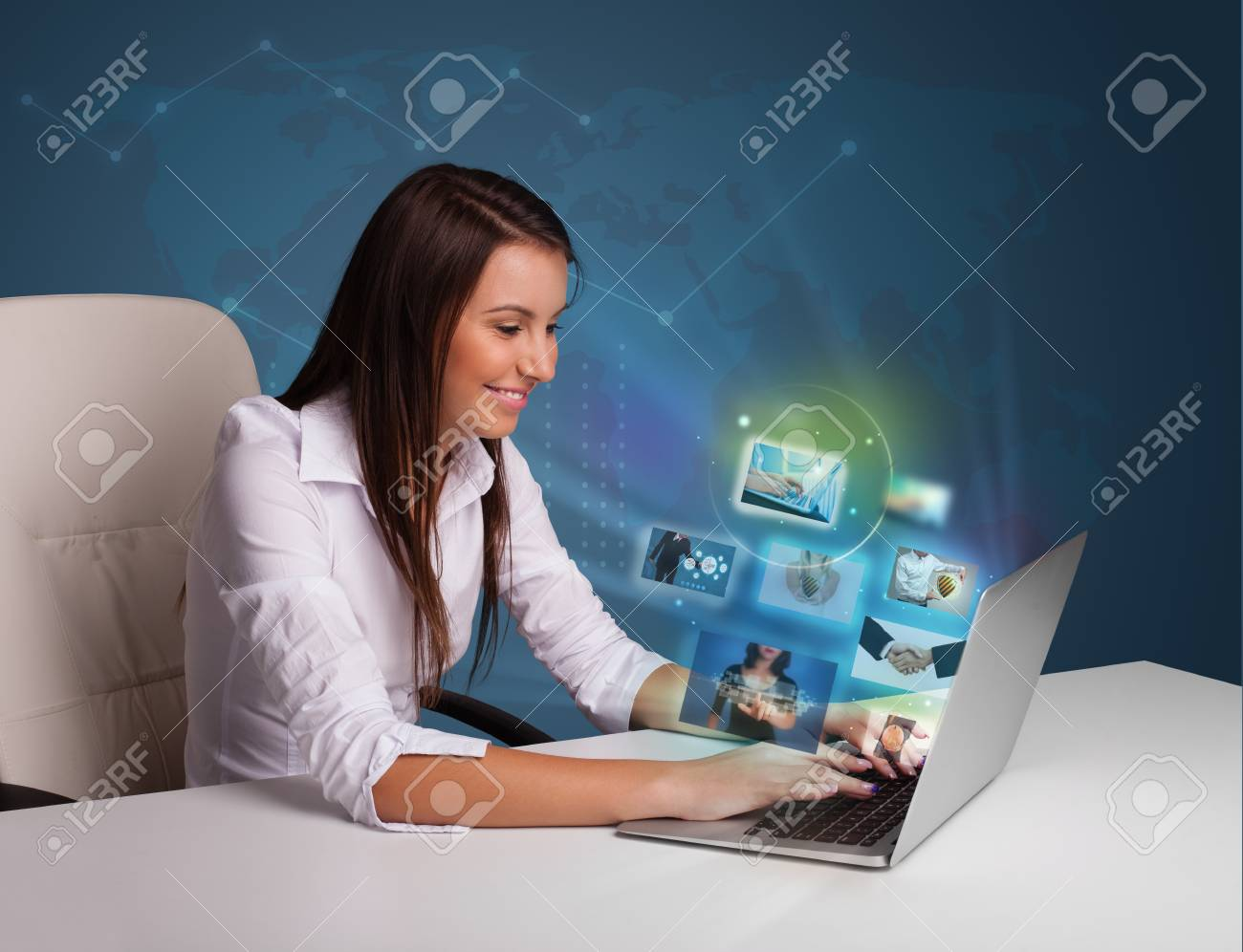 Beautiful young girl sitting at desk and watching her photo gallery on laptop Stock Photo - 17340066