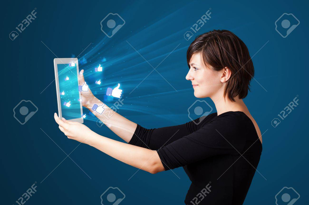 Young business woman looking at modern tablet with abstract lights and social icons Stock Photo - 17738397