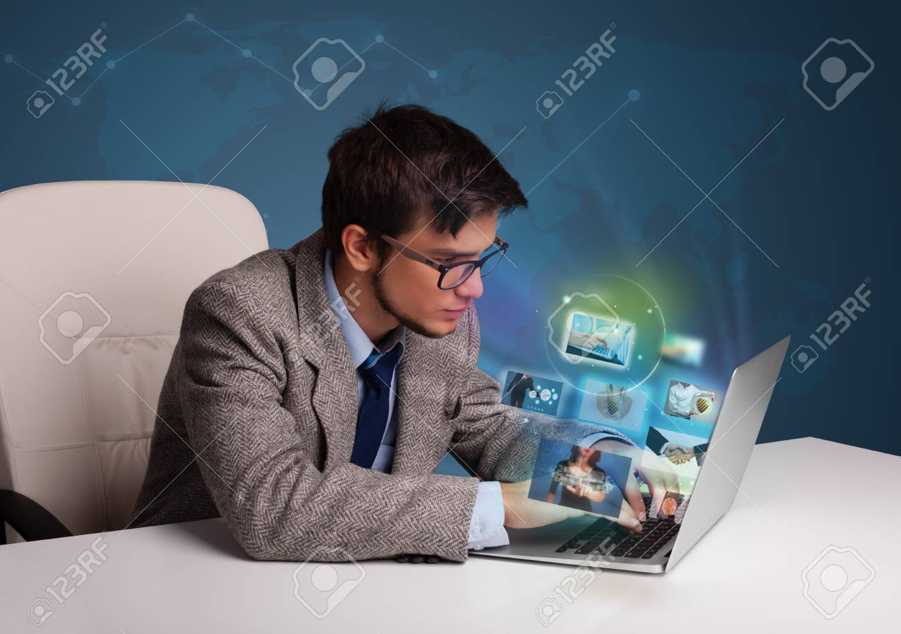Attractive young man sitting at desk and watching his photo gallery on laptop Stock Photo - 19270780