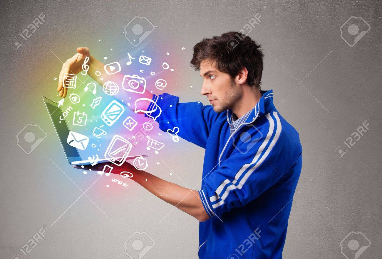 Casual young man holding laptop with colorful hand drawn multimedia symbols Stock Photo - 19374315