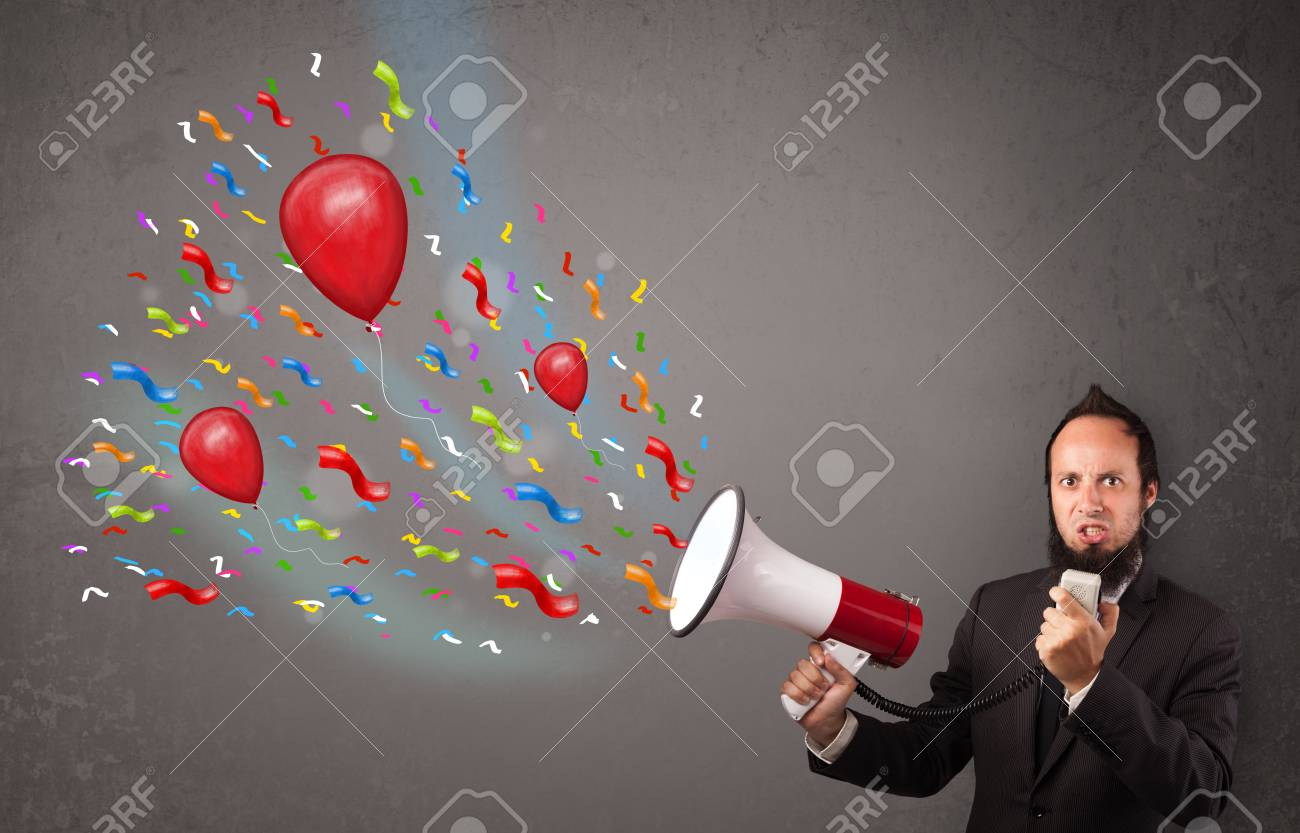 Young guy having fun, shouting into megaphone with balloons and confetti Stock Photo - 21740358