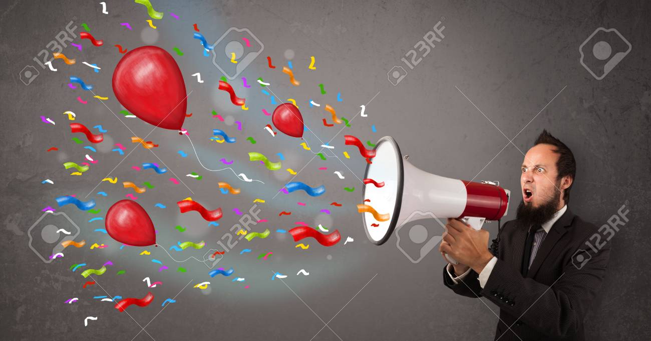 Young guy having fun, shouting into megaphone with balloons and confetti Stock Photo - 21893427