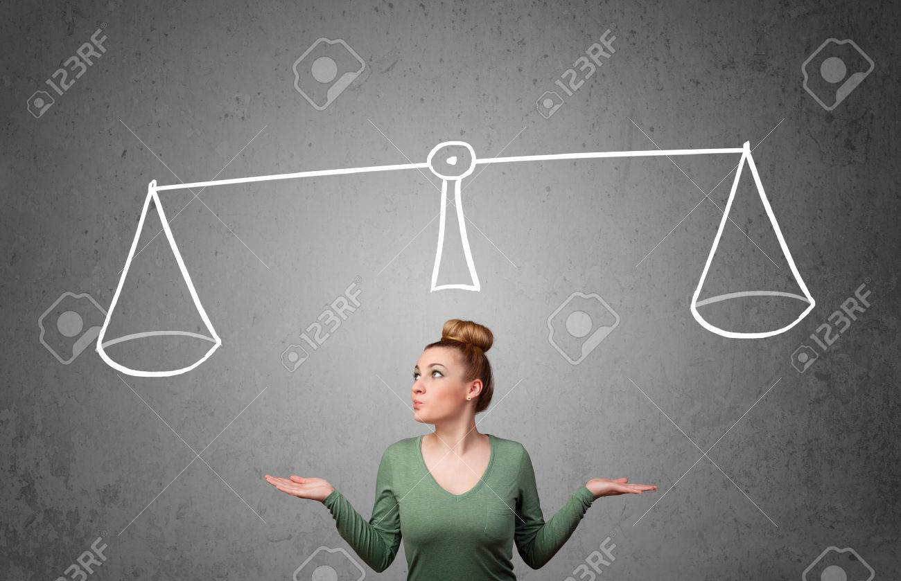 Pretty young lady taking a decision with scale above her head - 22959396