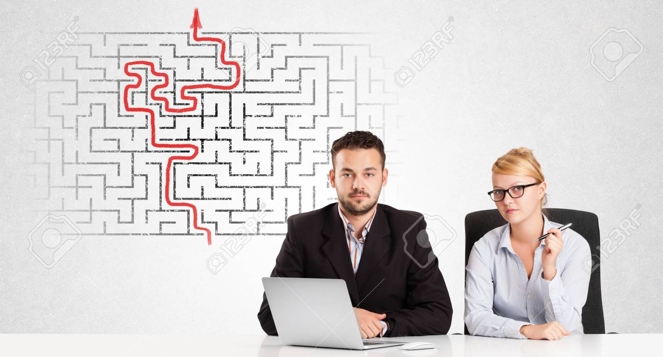 Business persons at desk with labyrinth in the background Stock Photo - 24636754