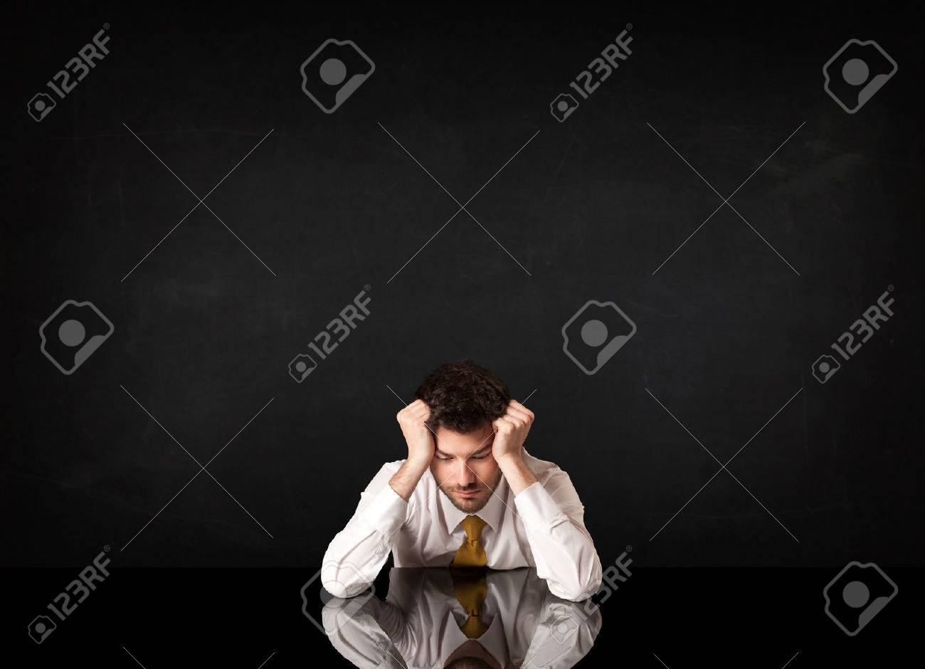 Depressed businessman sitting at a desk Stock Photo - 37300728
