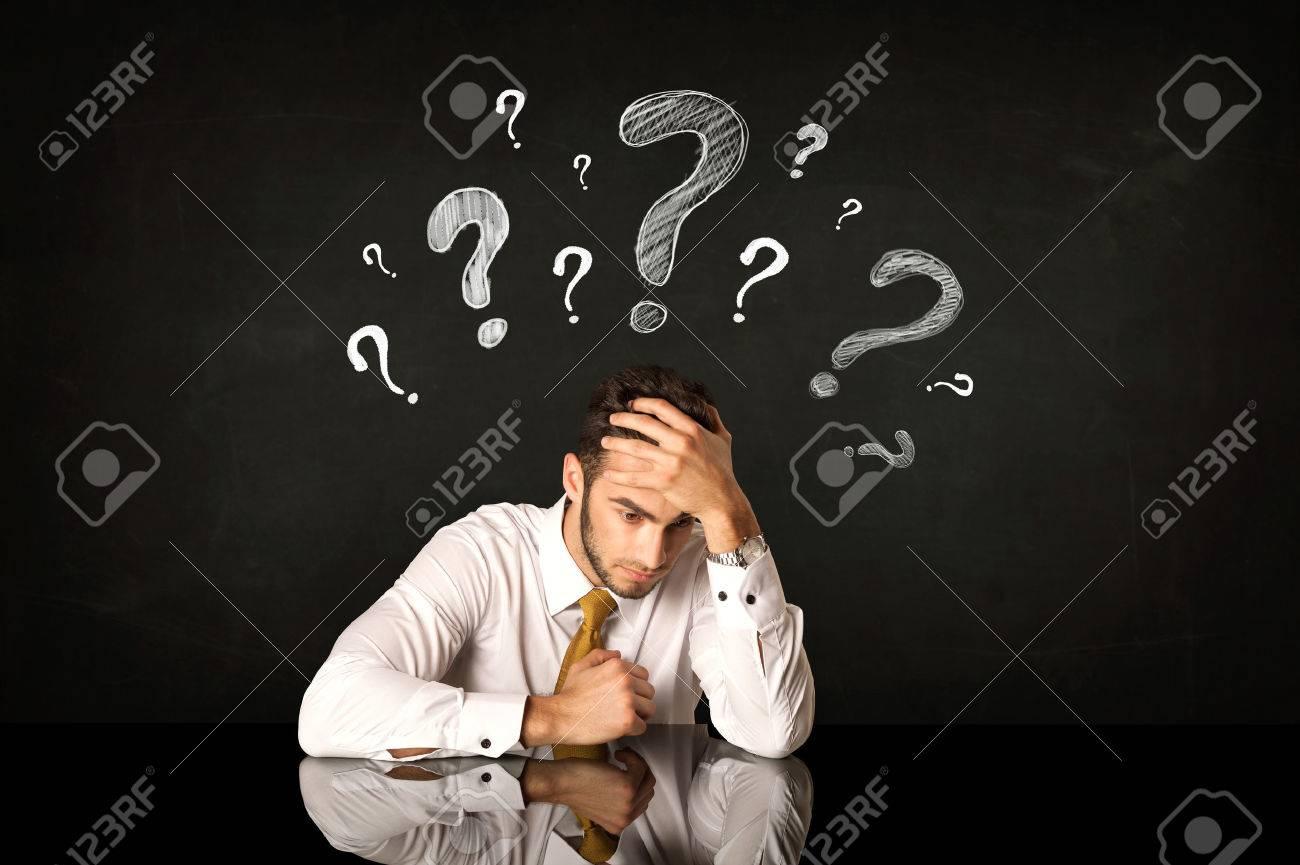 Depressed businessman sitting under question marks Stock Photo - 40355395