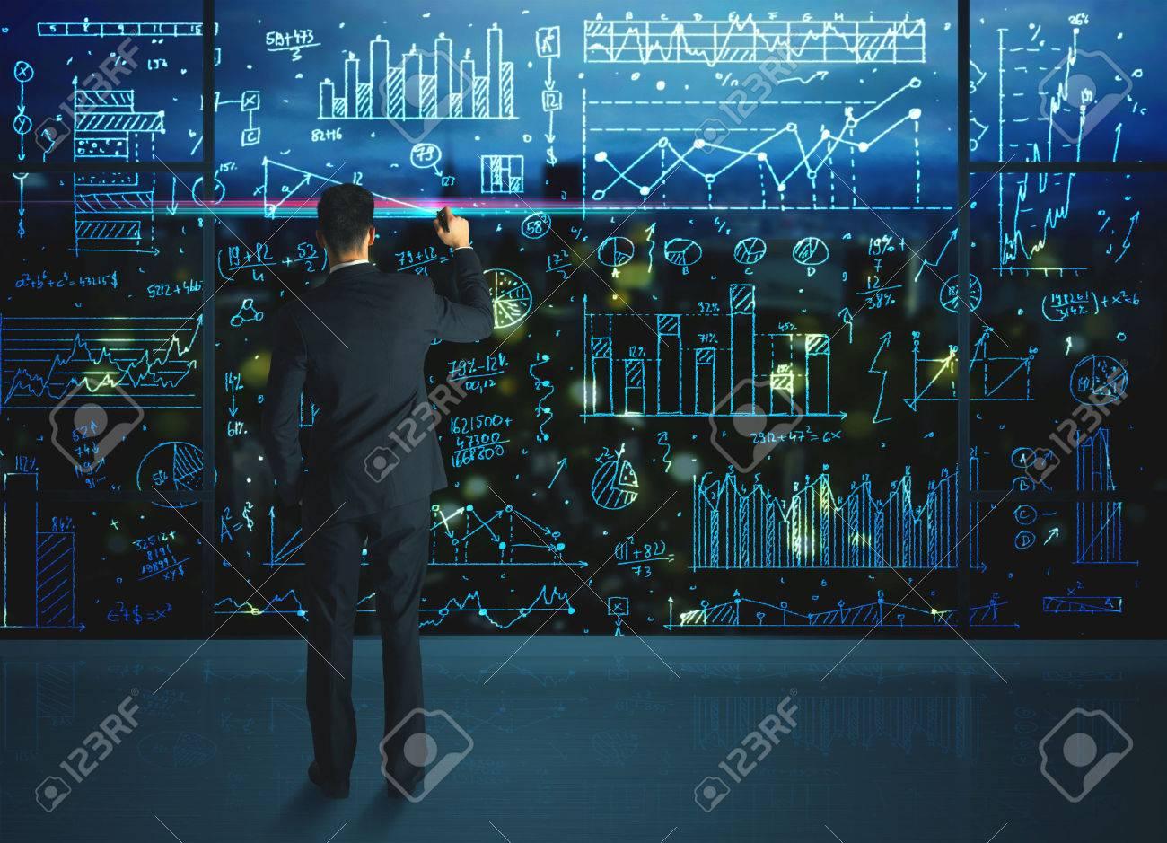 dibujo estadsticas de las empresas sobre la pared de vidrio del hombre de negocios foto de