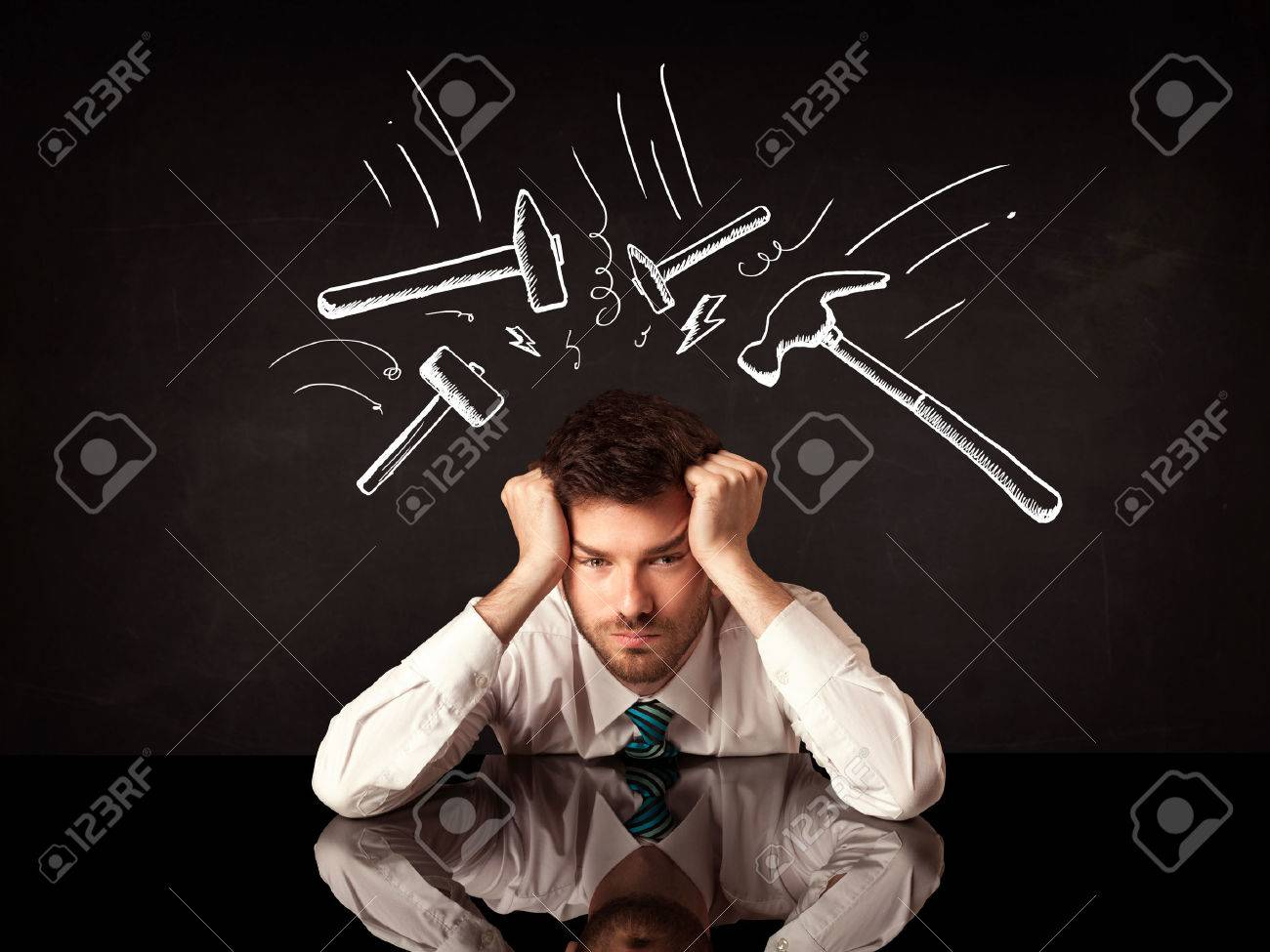 Young depressed businessman sitting under white drawn beating hammer marks Stock Photo - 46349270