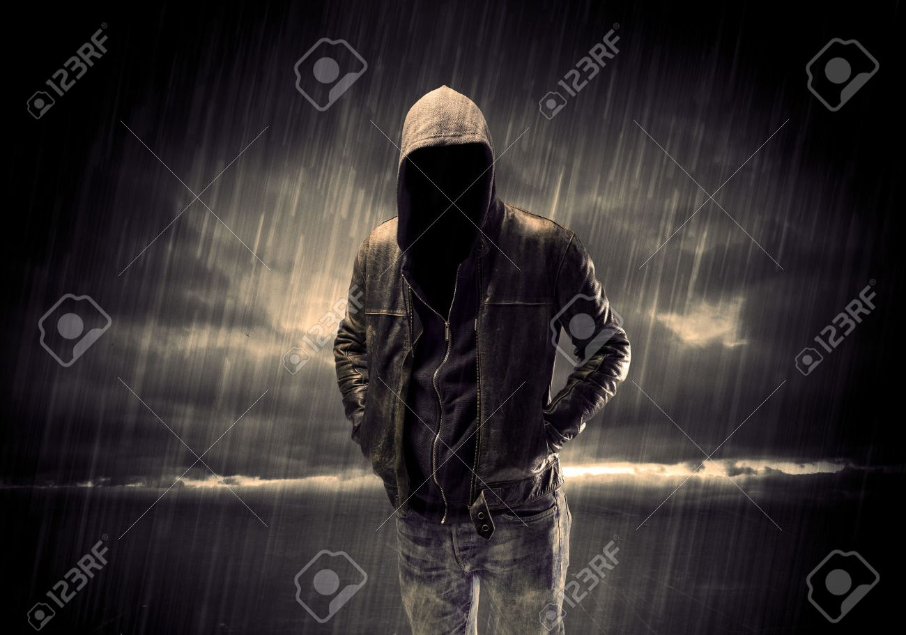 A faceless thief in unrecognizable hoodie standing in the middle of the night in the rain in front of landscape concept Stock Photo - 48402623
