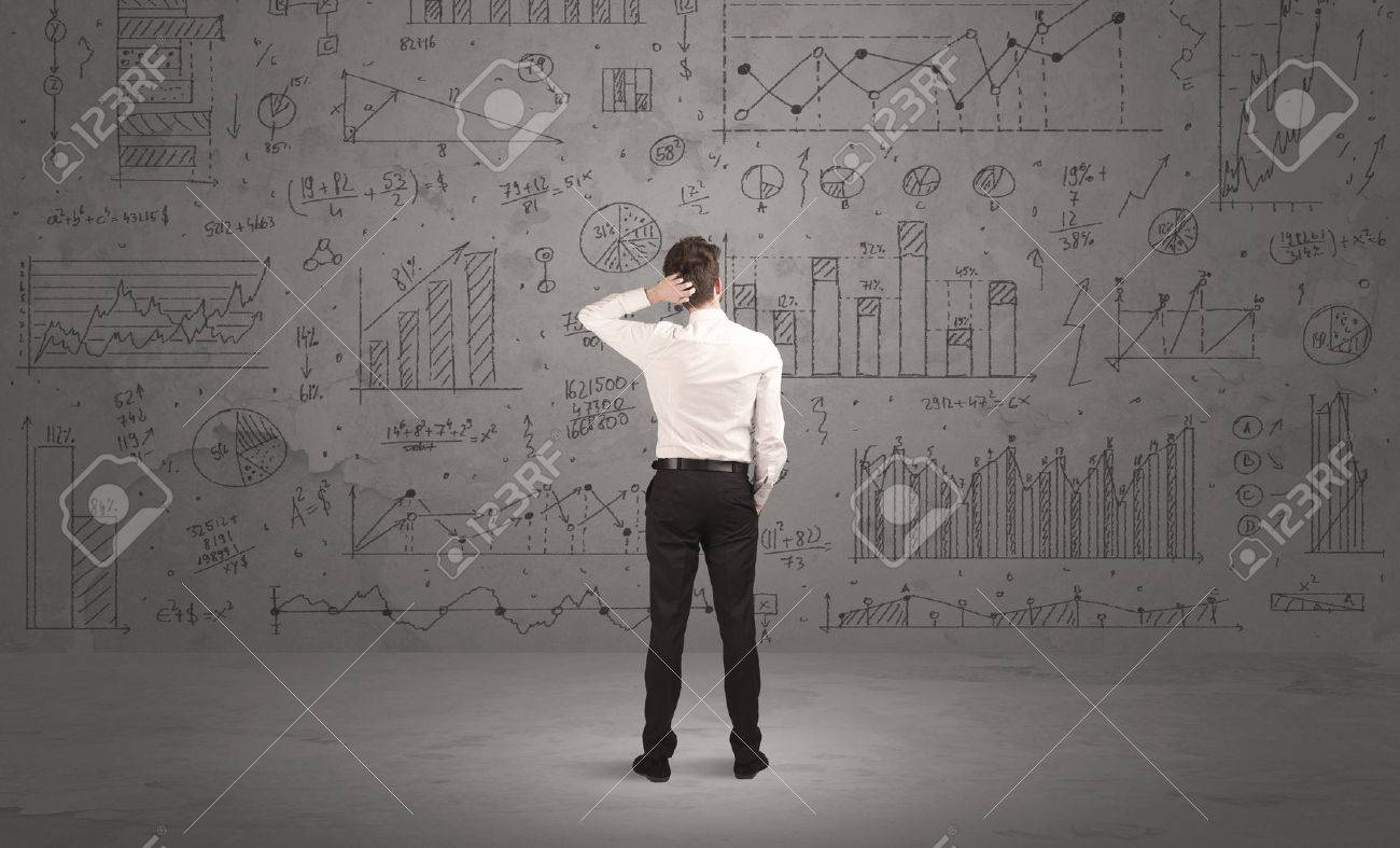 A successful confident businessman thinking about decisions, standing in front of wall full with graph pie charts and calculations concept Stock Photo - 48440560