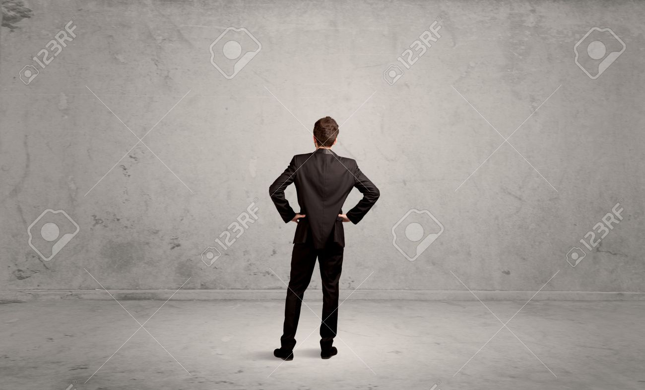 A confused sales person having a dilemma, standing with his back in empty grey urban environment concept Stock Photo - 48440566