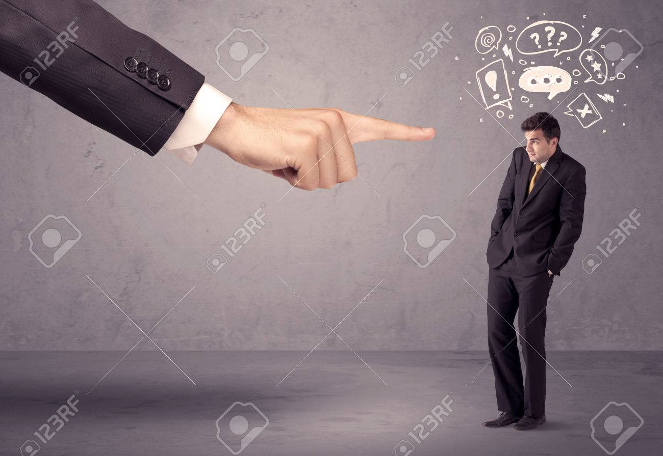 A young confused businessman being fired by large boss hand concept with drawn speech bubbles, exlamation, question marks Stock Photo - 48440953