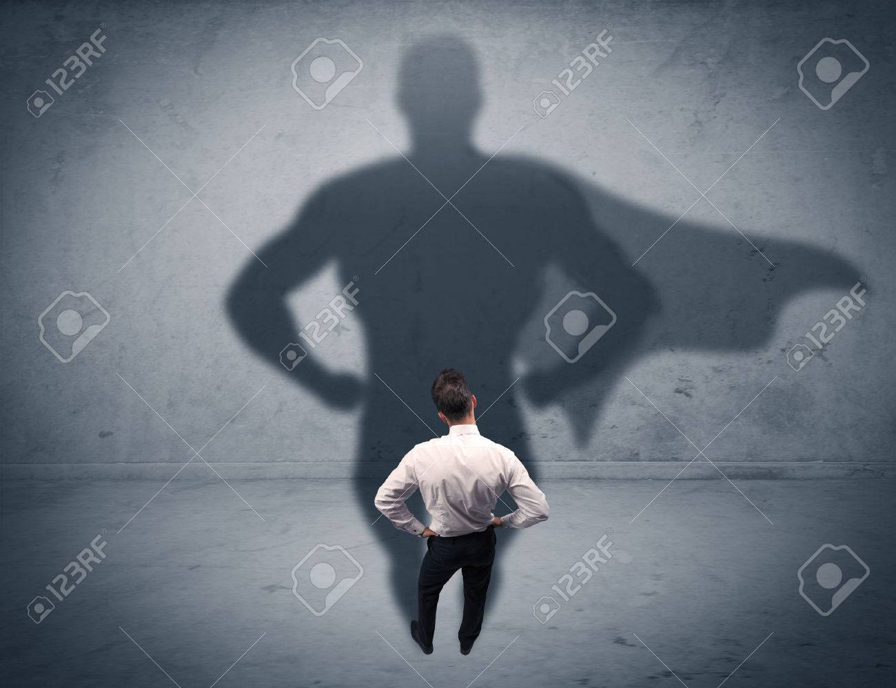 A confident young elegant salesman with briefcase facing a wall, looking at his super hero shadow concept Stock Photo - 48982473