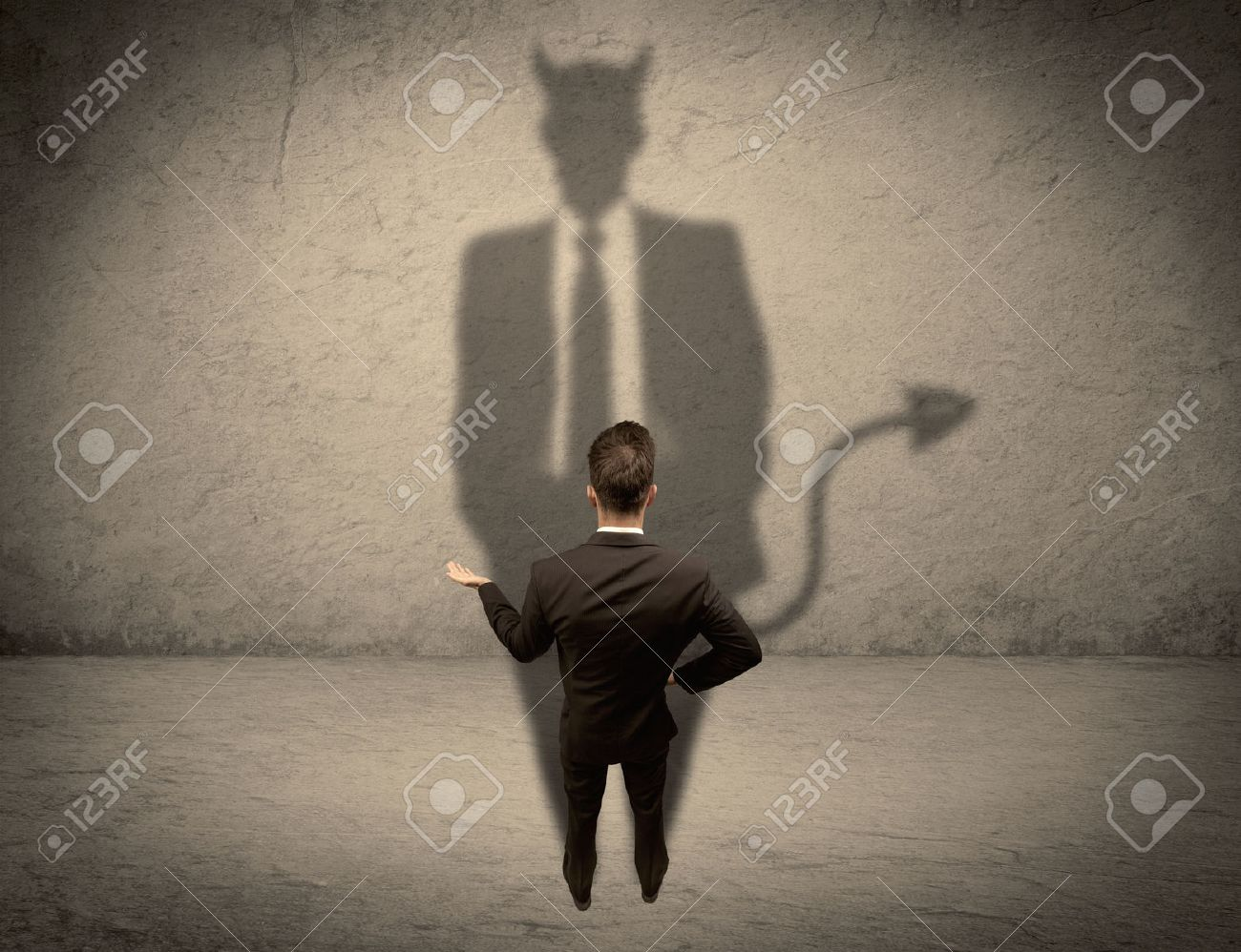 An experienced tricky businessman in suit looking at his devil desguise shadow reflected on the wall concept Stock Photo - 49618459