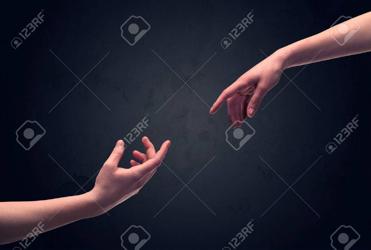 Two male hands reaching out to one another, almost touching, in front of dark clear empty background wall concept Stock Photo - 49618535