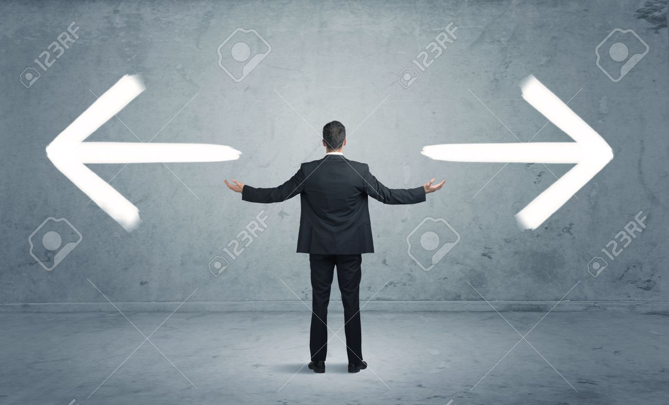 A businessman in doubt, having to shoose between two different choices indicated by arrows pointing in opposite direction concept - 50096504