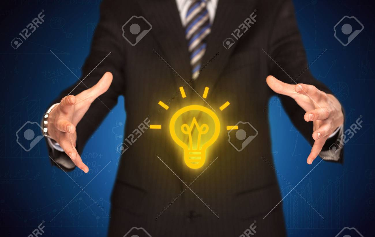 A creative businessman has a great bright idea illustrated by holding a drawn light bulb in the hand concept - 51382376