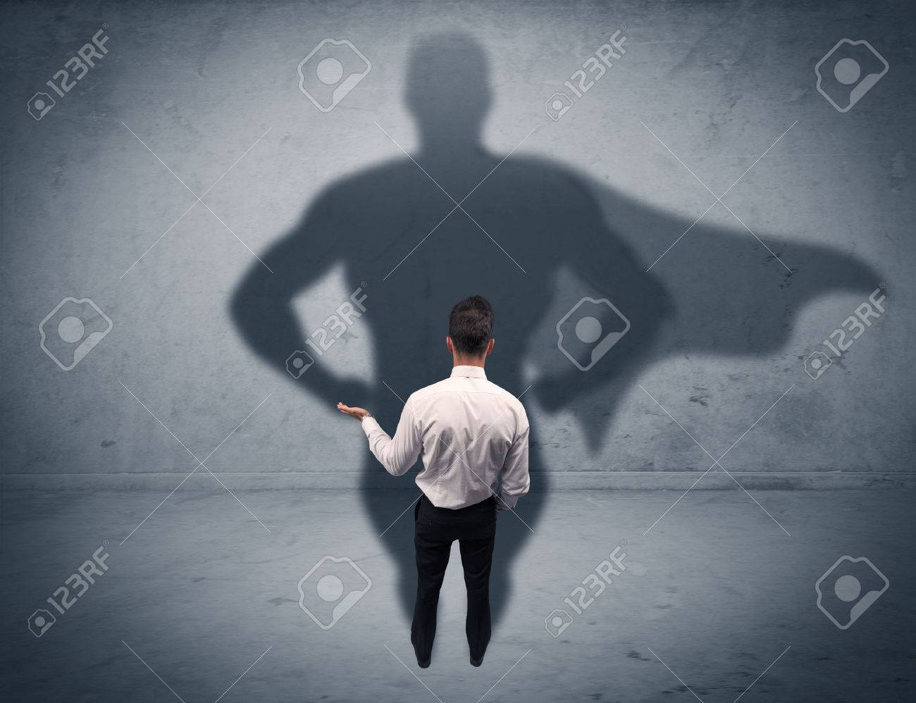 A confident young elegant salesman with briefcase facing a wall, looking at his super man shadow concept Stock Photo - 52603940