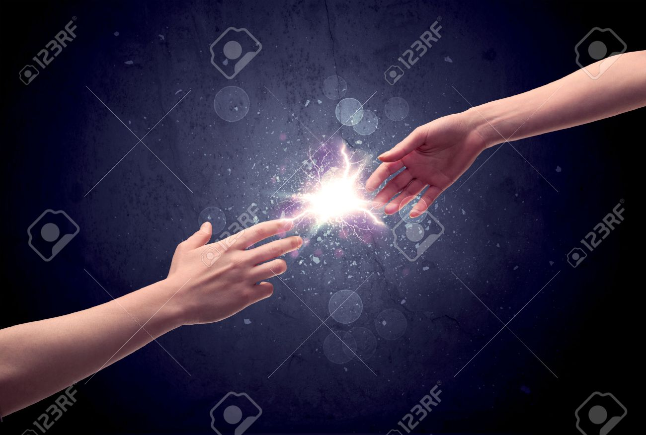 Two male hands reaching towards each other, almost touching with fingers, lighting spark in galaxy background concept Stock Photo - 54140960