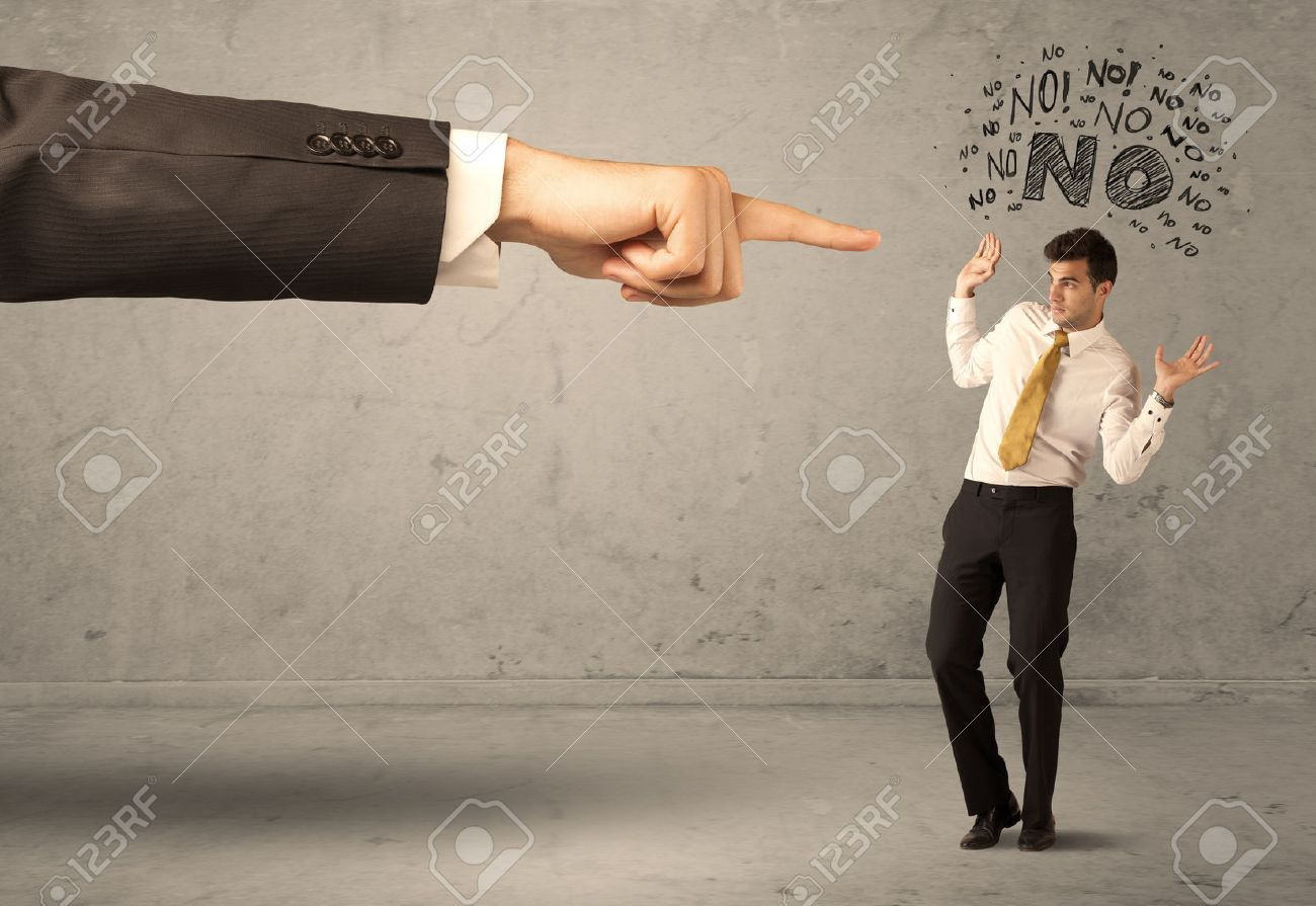 A young employee disagreeing and arguing with boss, feeling ashamed concept. A large hand pointing at businessman saying no Stock Photo - 55112537