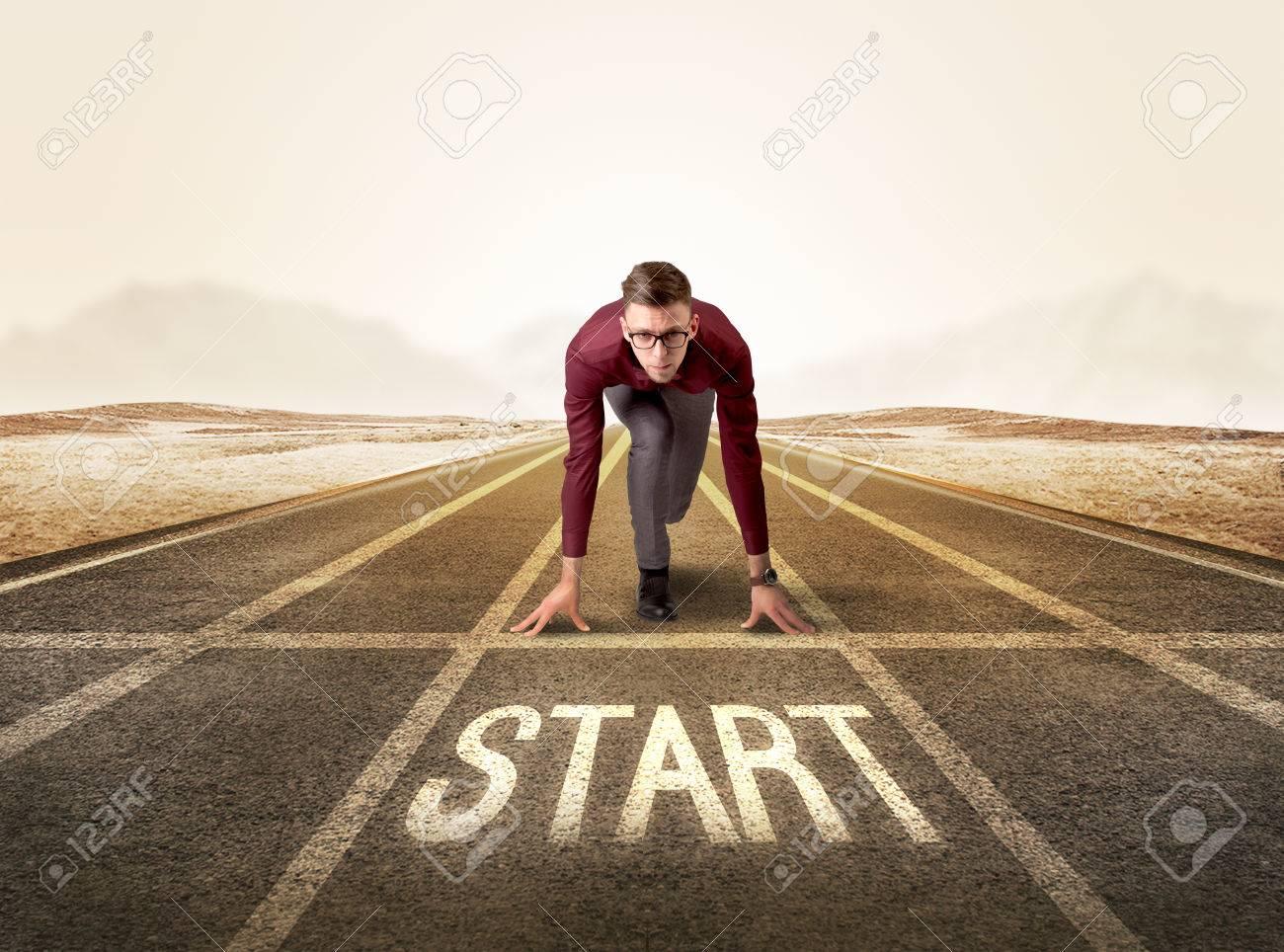 ff09de988 Young determined businessman kneeling before start line