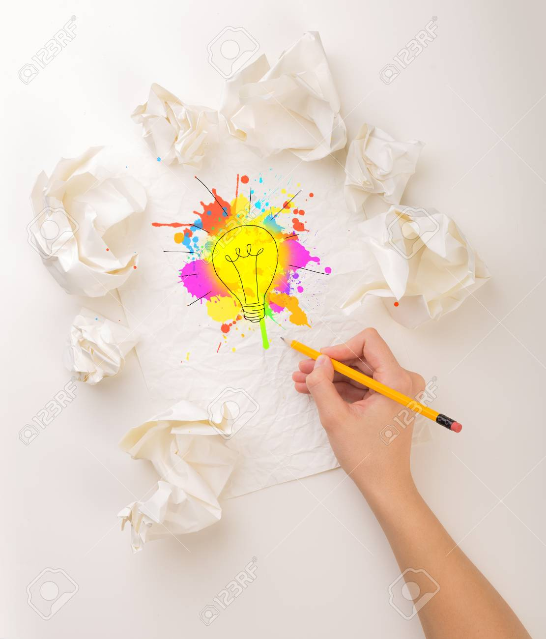 female hand next to a few crumpled paper balls drawing a colorful