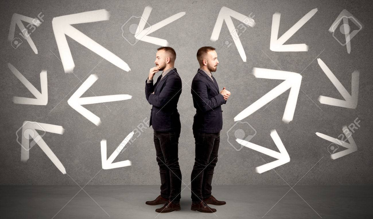 Young conflicted businessman choosing between two directions with arrows around him - 81655413