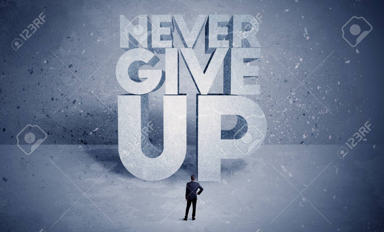 a stressed out business worker standing in front of huge block letters saying never give up