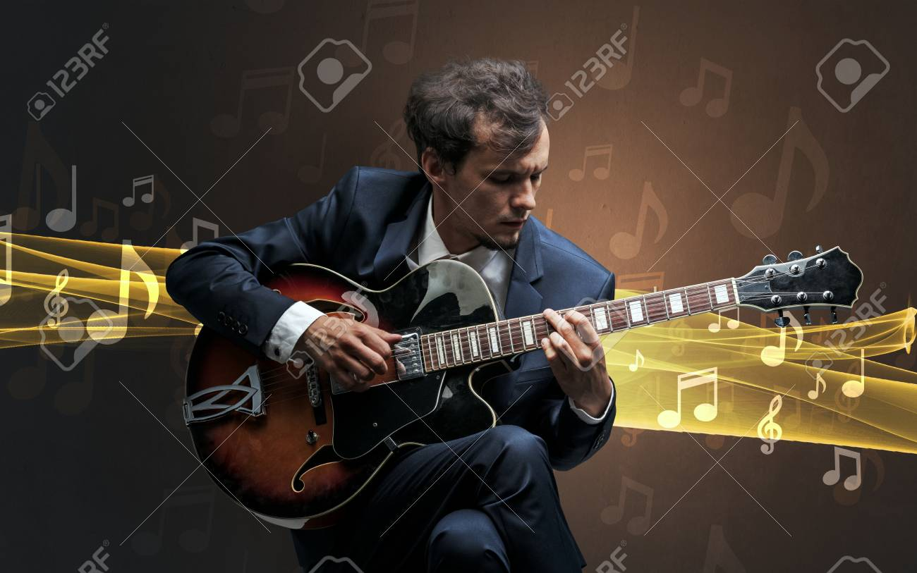 Young male musician playing on his guitar with musical notes around - 95808082