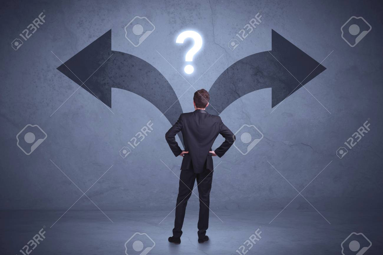 Businessman taking a decision while looking at arrows on the wall concept background - 96750373