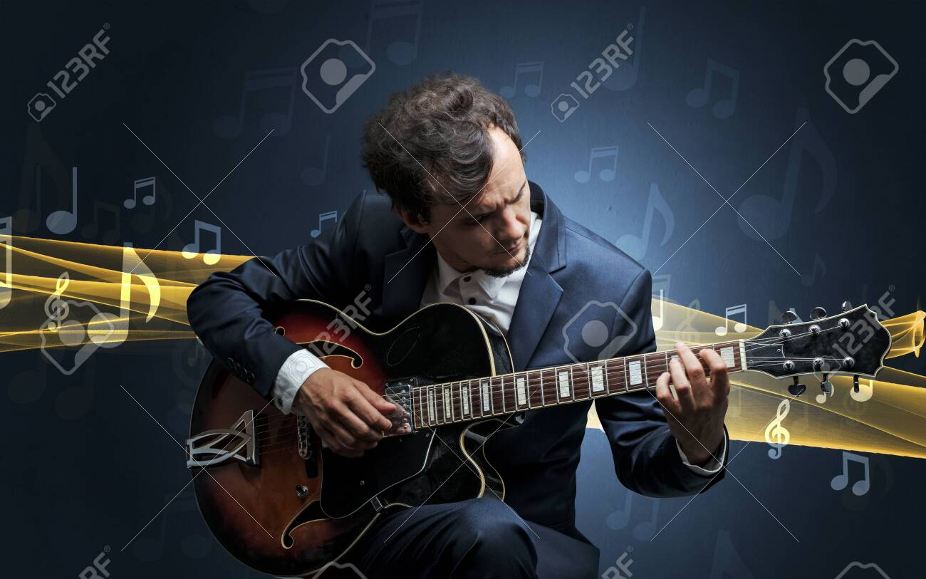 Young male musician playing on his guitar with musical notes around - 119157472