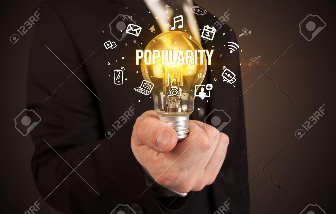 Businessman holding light bulb with POPULARITY inscription, social media concept - 155383560