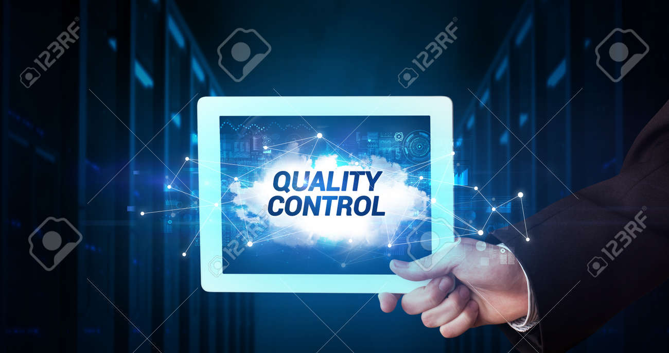 Young business person working on tablet and shows the inscription: QUALITY CONTROL - 156113201