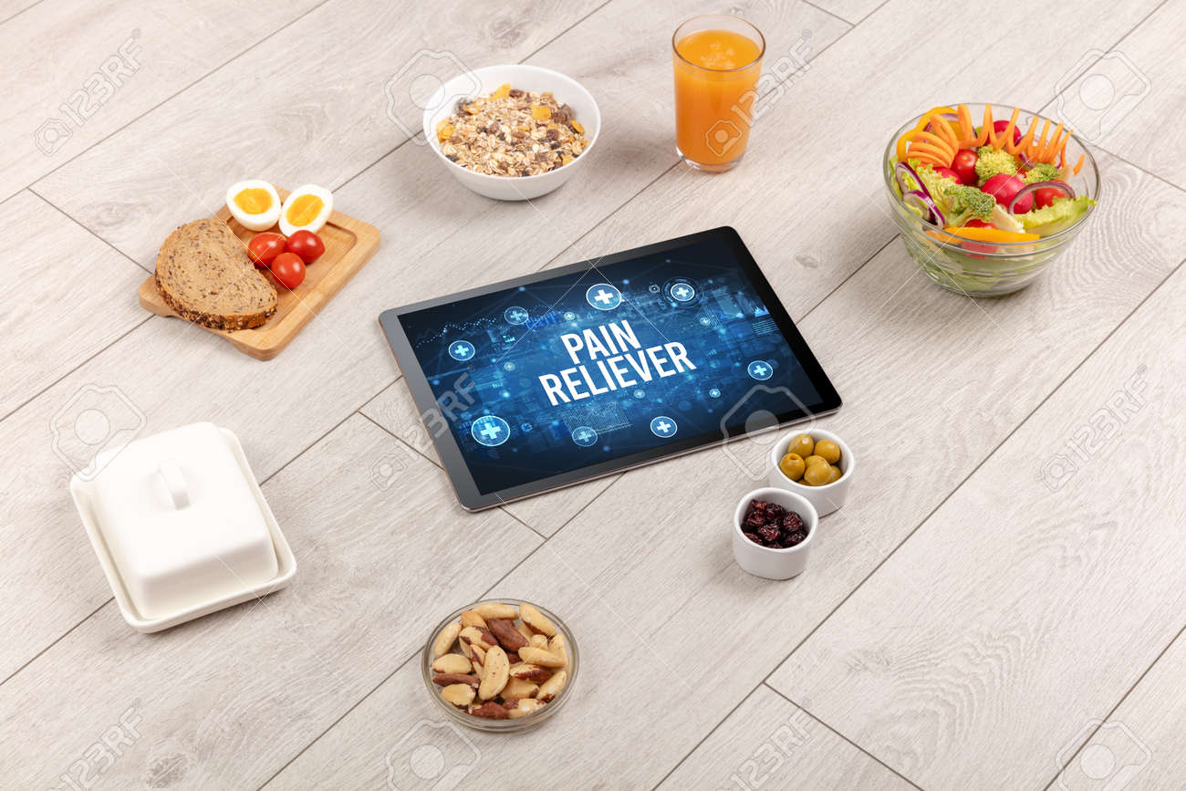 PAIN RELIEVER concept in tablet pc with healthy food around, top view - 162889727