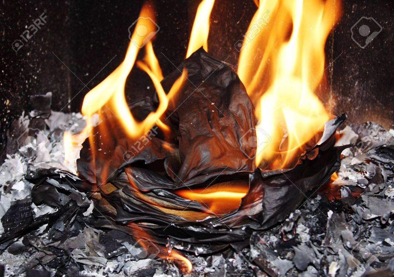 tongues of flame on burning sheets of paper in a fireplace fire