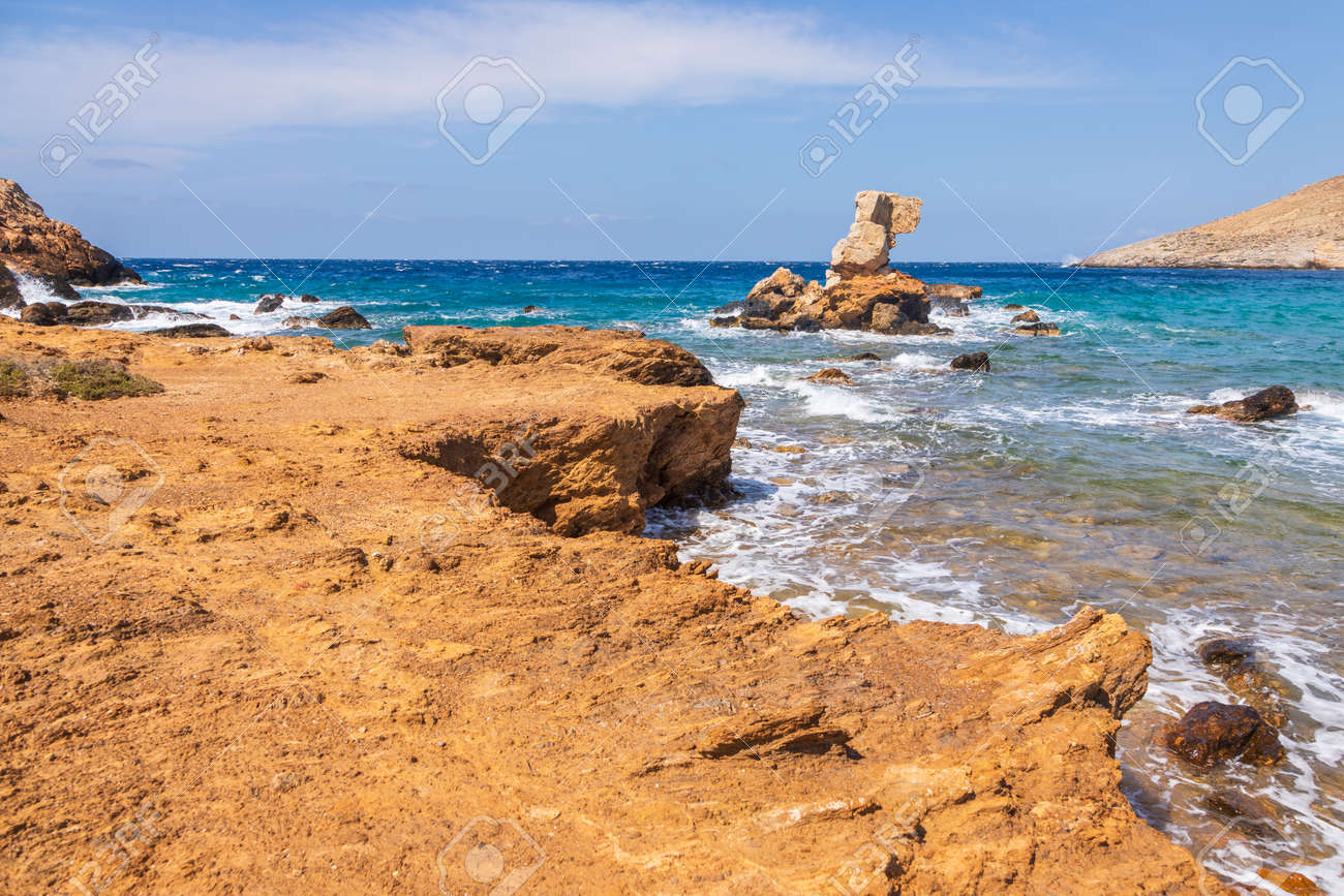 Rocky coast wit characteristic formation on the north of the island of Ios. Colorful boats on the beach. A white, traditional Greek church in the background. Greece. - 158864335
