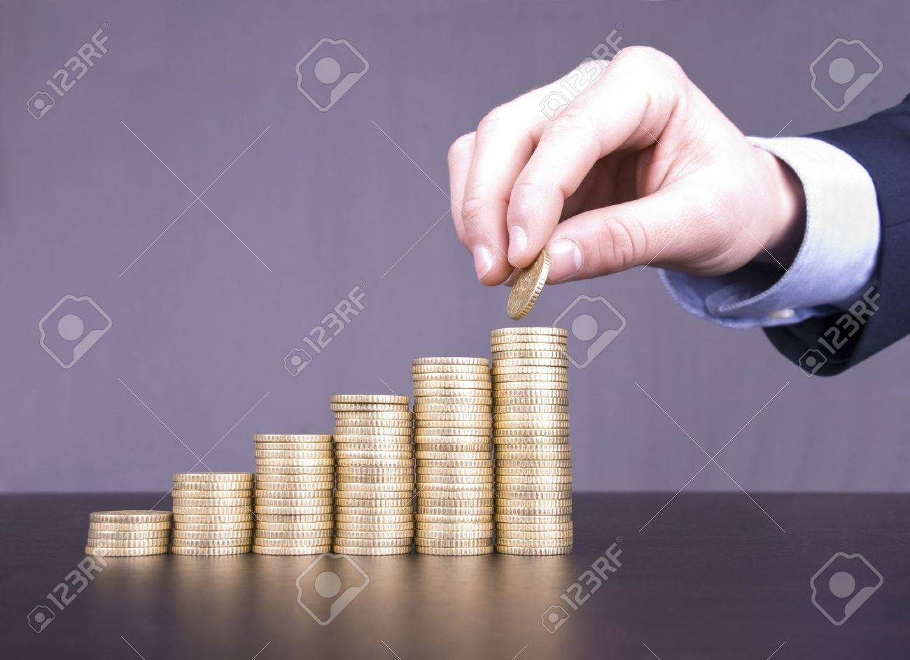 Male caucasian hand stacking coins in a staircase Stock Photo - 17075878