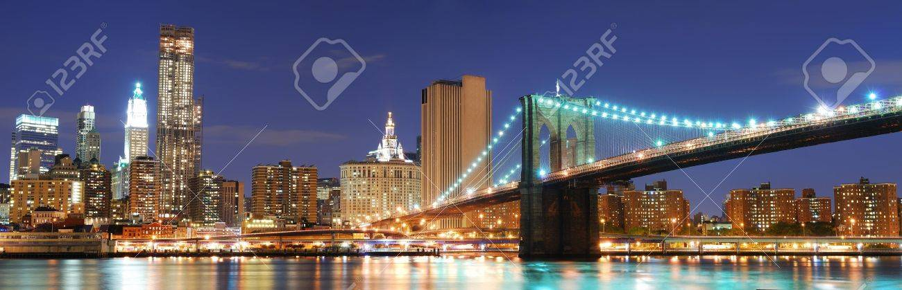 New York City Manhattan skyline panorama with Brooklyn Bridge and office skyscrapers building in at dusk illuminated with lights at night Stock Photo - 7530681
