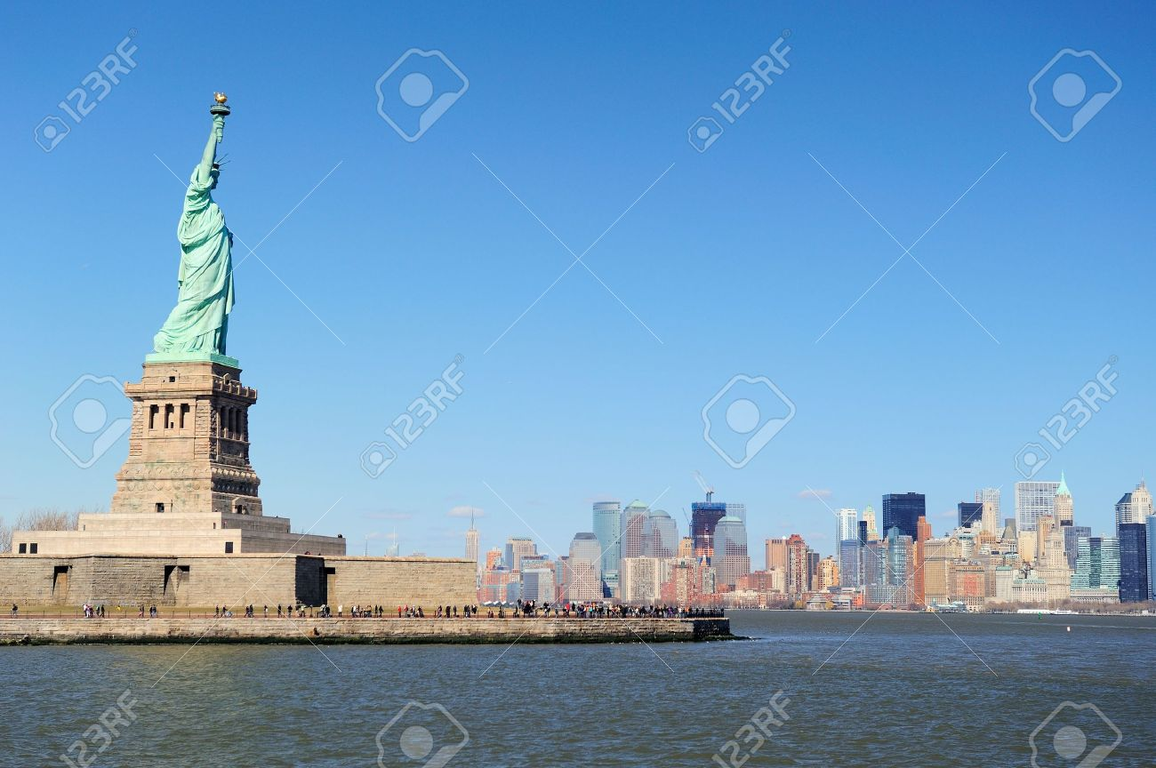 Statue of Liberty faces New York City Manhattan downtown skyline with skyscrapers over Hudson River with clear blue sky. Stock Photo - 9480635