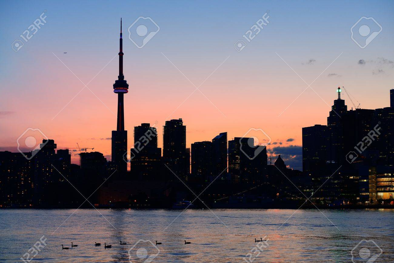Toronto city skyline silhouette at sunset over lake with urban skyscrapers. Stock Photo - 17398312