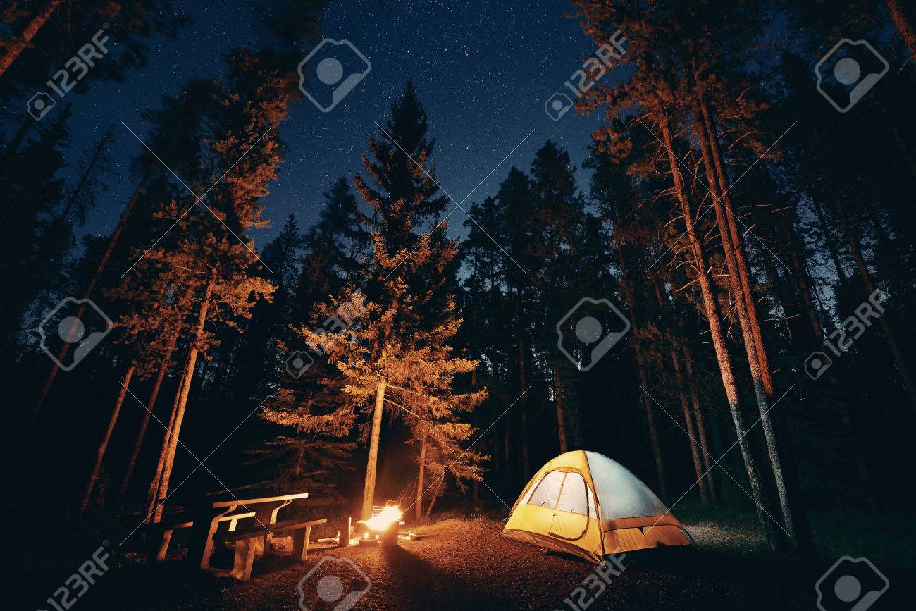 Camping under stars with bonfire and tent in Banff National Park - 62034323