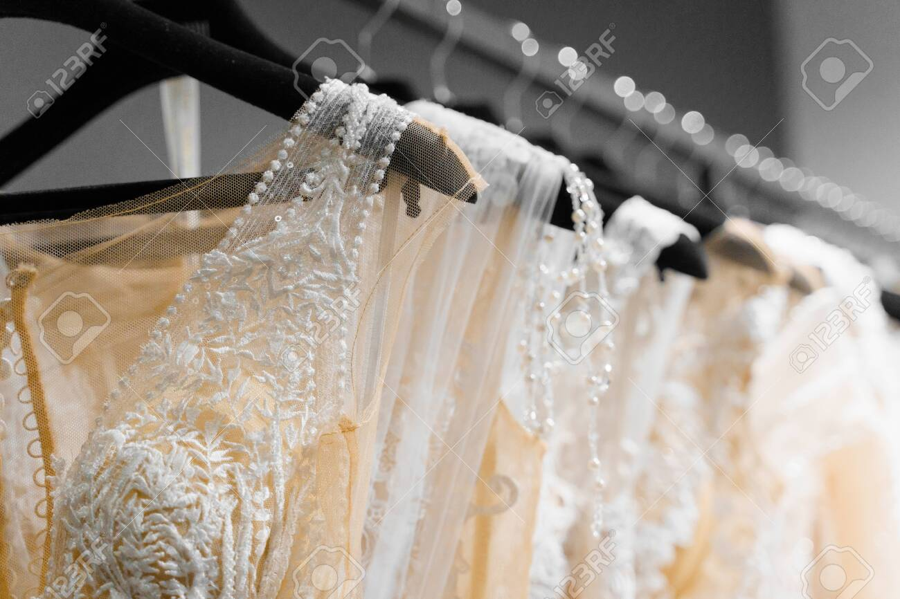 Cloth of wedding dresses made of silk chiffon, tulle and lace. Beautiful White cream bridal dress on hangers in wedding salon. Pearls and crystals pendants on the sleeves of a wedding dress - 148069071