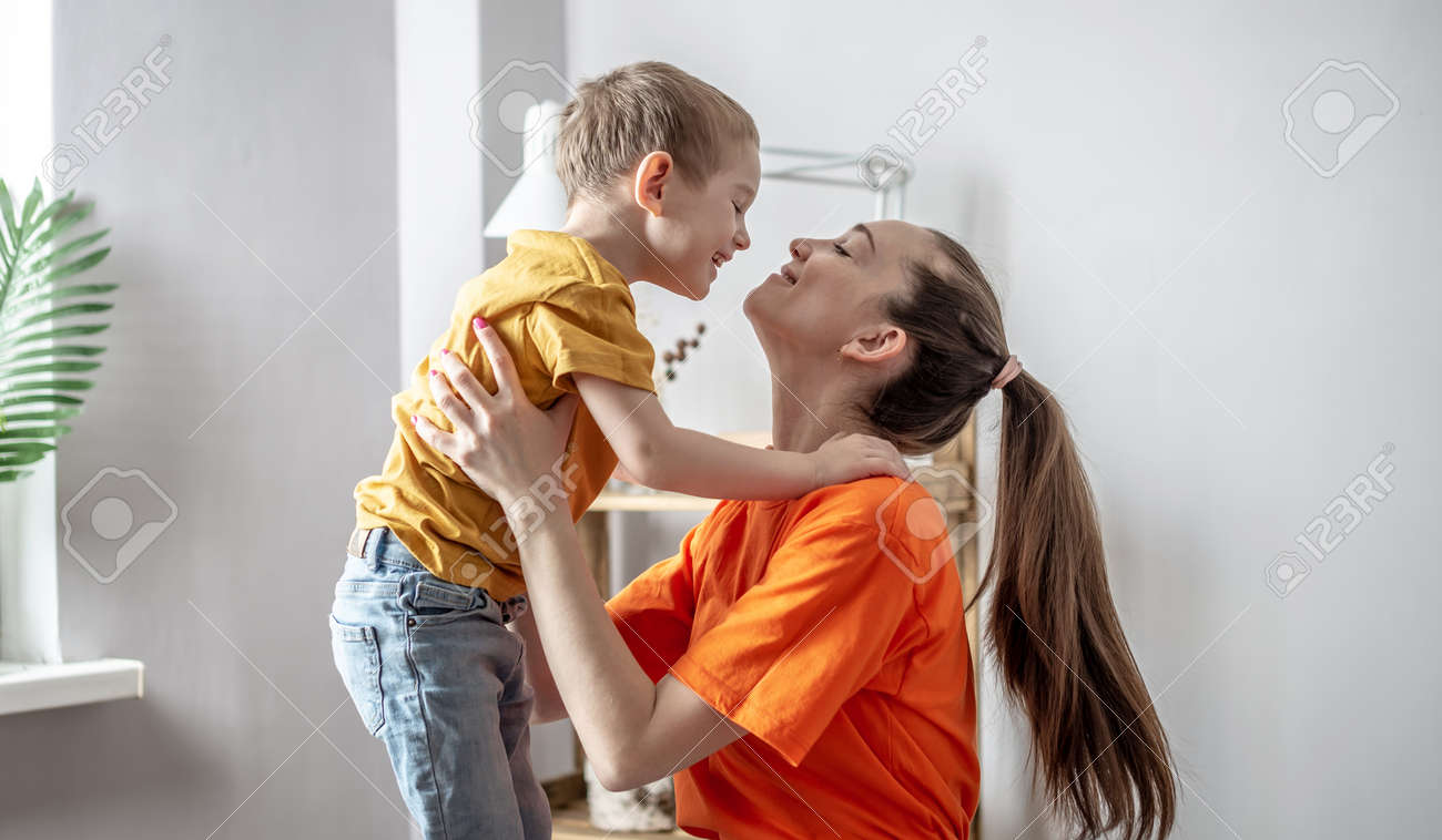 Mother and child wearing in bright clothes are tenderly hugging each other. Concept of a happy harmonious family, caring and pastime with children. - 167507050