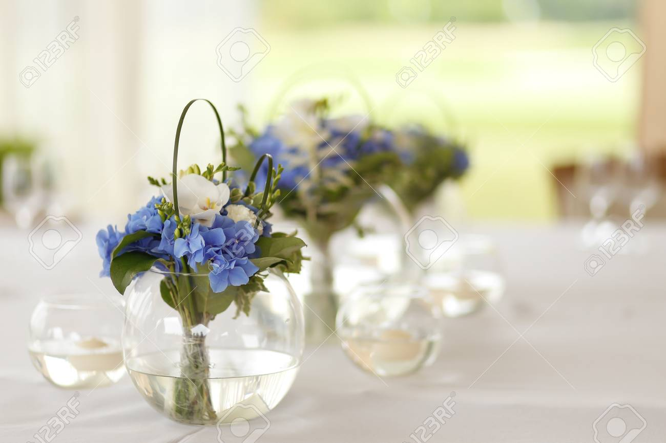 Wedding Decoration Of Blue And White Flowers In The Round Glass