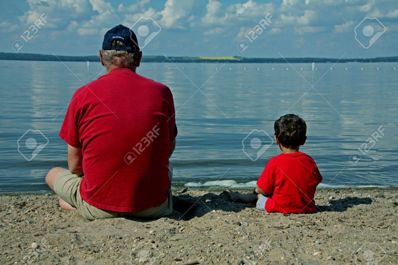 a man and a boy in red shirts on the beach at a lake Stock Photo - 17123651