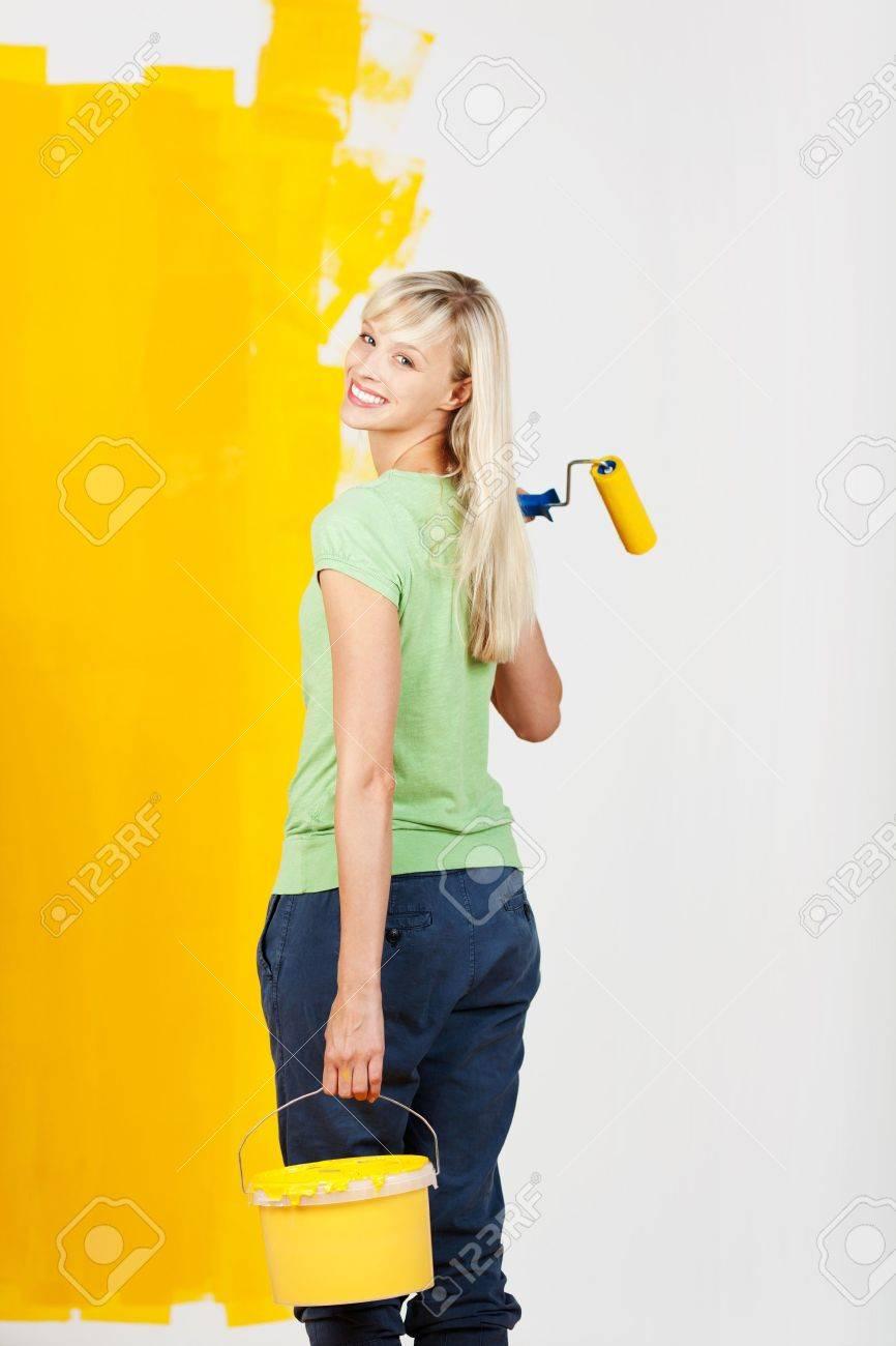 Lachende jonge vrouw met gele verf in een container en een rol in ...