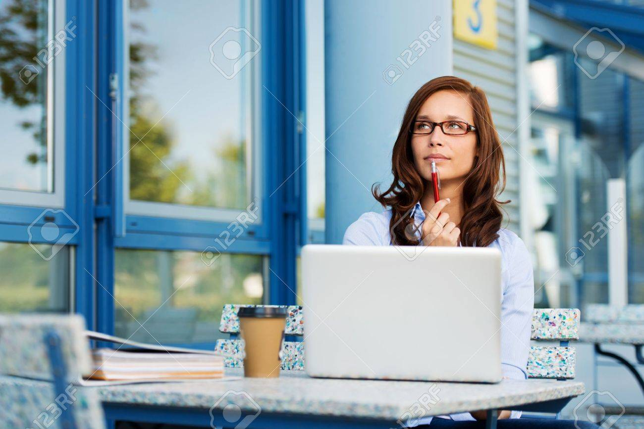 Photo of pretty woman fiddling with pen and thinking over a subject while sitting in some coffee shop with her laptop. Stock Photo - 20736020