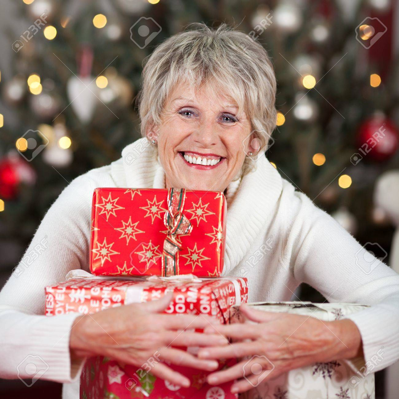 Laughing Beautiful Senior Woman Hugging A Pile Of Christmas Gifts ...